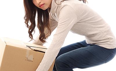 【腰痛】悪い姿勢で重いダンボールを持つ女性