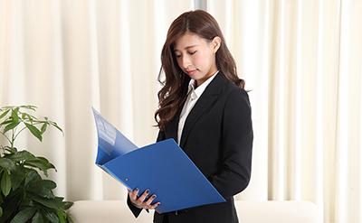 【生活】仕事の書類をながめるビジネススーツ女性