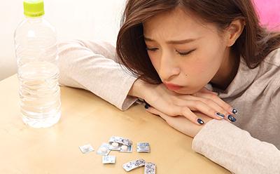 【頭痛】頭痛薬とにらめっこする女性(アップ)